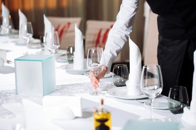 ゲストを受け入れる準備をしているレストランのウェイターサービングテーブル。