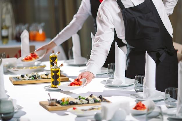 Официант сервирует стол в ресторане, готовится к приему гостей.