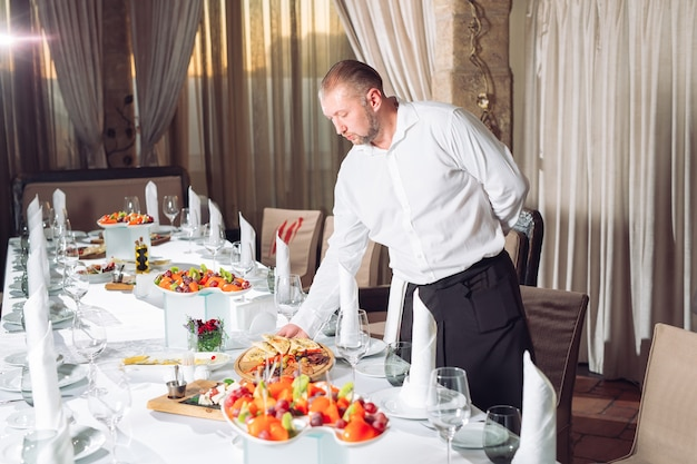 Waiter serving table in the restaurant preparing to receive guests.