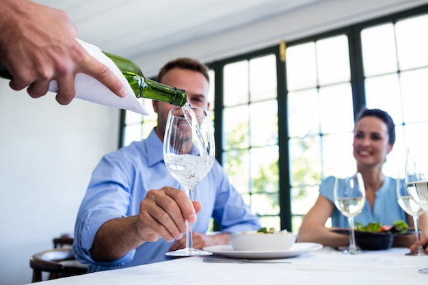 Waiter serving wine to group of friends while having lunch