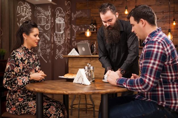Cameriere che serve giovane coppia con croissant. appuntamento in un bellissimo pub.
