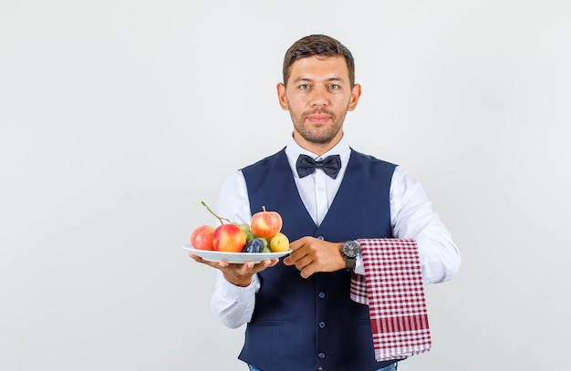 Waiter in shirt, vest, bow tie, holding plate full of fruits and looking cheery , front view.