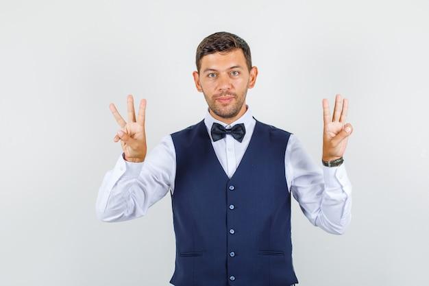 Cameriere in camicia, gilet che gesticola tre dita e aspetto mite, vista frontale.