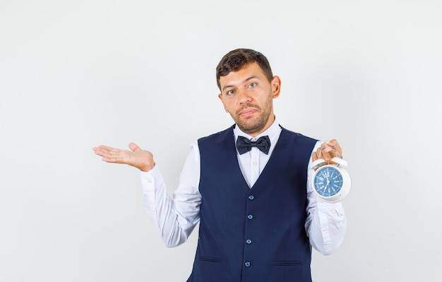 Waiter in shirt, vest holding alarm clock with gesture and looking helpless , front view.