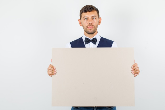 Waiter in shirt, vest holding blank canvas and looking serious , front view.