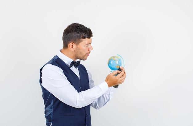 Cameriere in camicia, gilet che tiene e guardando il globo del mondo, vista frontale.