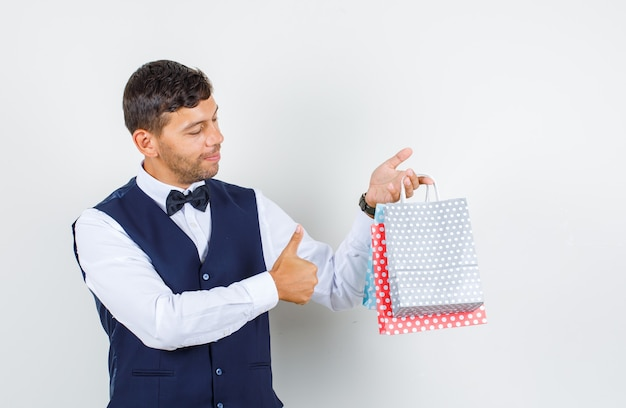 Waiter in shirt, vest holding paper bags with thumb up and looking positive , front view.