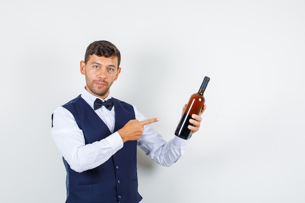 Waiter in shirt, vest pointing finger at alcohol bottle , front view.