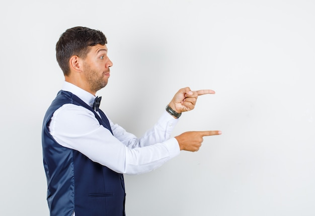 Waiter in shirt, vest pointing fingers to side and looking motivated .