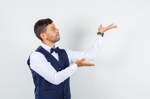 Cameriere in camicia, giubbotto che alza i palmi delle mani come in possesso di qualcosa e guardando concentrato, vista frontale.