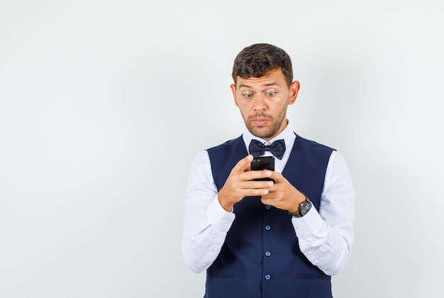 Waiter in shirt, vest using mobile phone and looking excited , front view.
