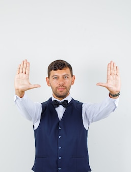 Waiter showing enough gesture and smiling in shirt, vest front view.