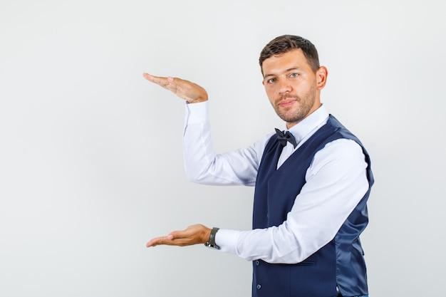 Официант показывает знак большого размера в рубашке, жилете, галстуке-бабочке, вид спереди.