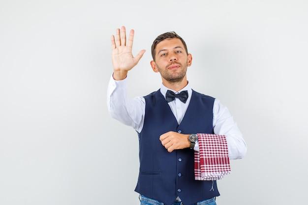 シャツ、ベスト、ジーンズで手のひらを見せて自信を持って見えるウェイター、正面図。
