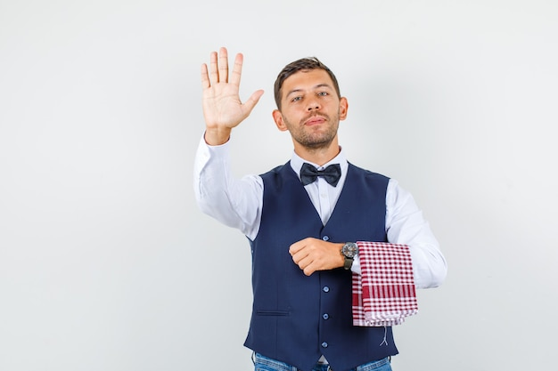 Waiter showing palm up in shirt, vest, jeans and looking confident , front view.