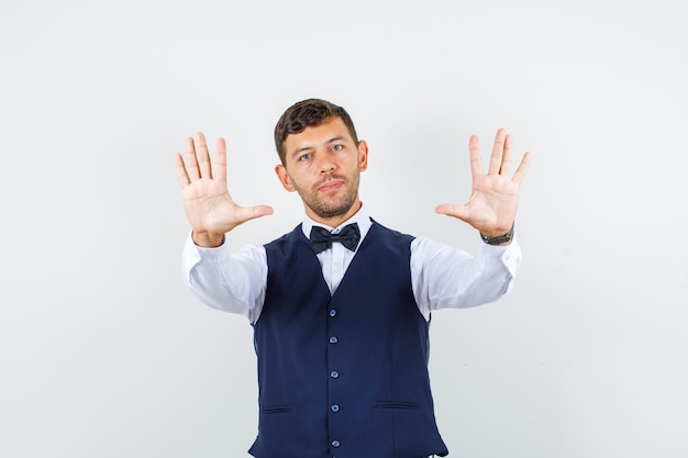 Waiter showing refusal gesture in shirt, vest and looking serious. front view.