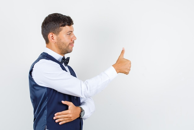 Waiter showing thumb up in shirt, vest and looking cheerful. front view.