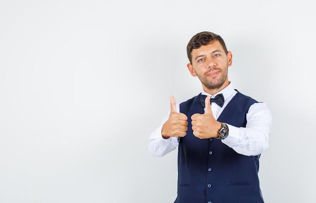 Официант показывает палец вверх в рубашке, жилете и выглядит веселым. передний план.