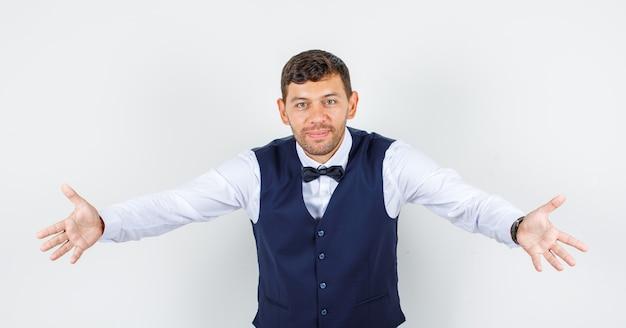 Cameriere allargando le braccia come abbracciare qualcuno in camicia, gilet e sembrare allegro. vista frontale.