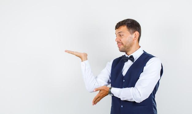 手のひらを脇に広げてシャツを着て笑っているウェイター、ベストの正面図。