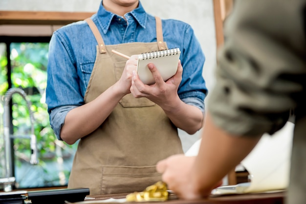 Waiter taking order from customer at counter in cafe