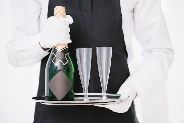 Waiter in uniform holding bottle with glasses