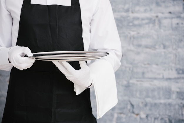Waiter in uniform holding metal tray