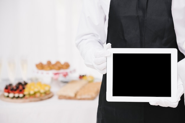 Waiter in uniform holding a tablet with mock-up