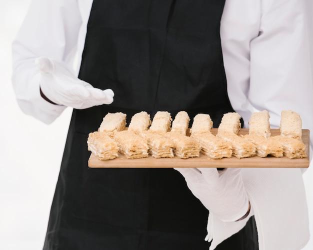 Waiter in uniform presenting desert