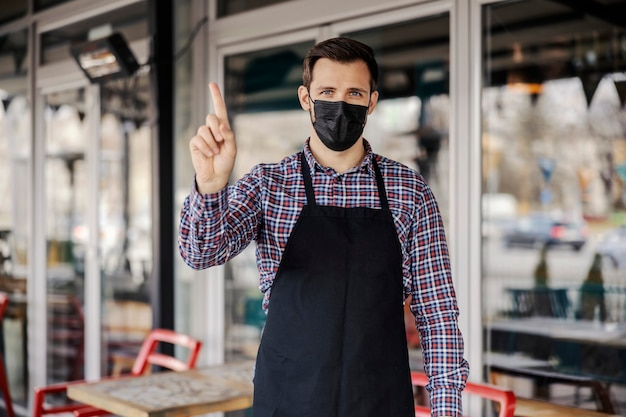 A waiter in uniform and with a protective face mask stands in front of the entrance to the restaurant and forbids entry without virus protection