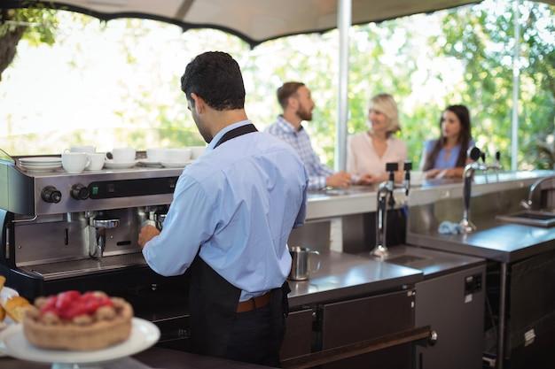 Официант, используя трамбовку, вдавливает молотый кофе в портафильтр