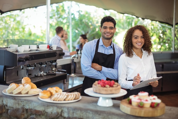 Waiter and waitress standing with clipboard at counter in restaurant