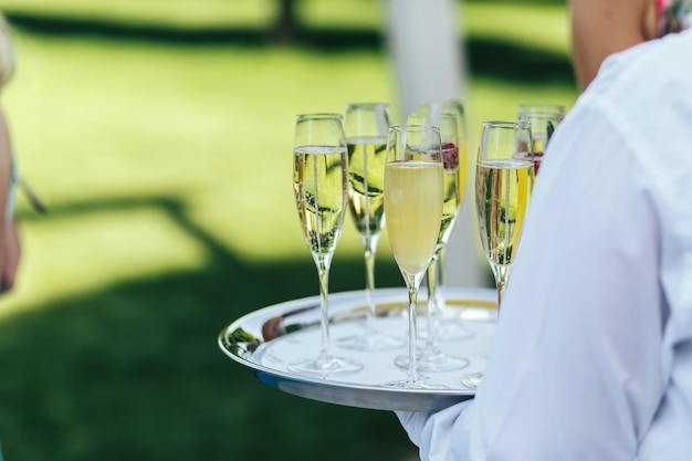 Waiter in white chirt holds a tray with champagne flutes