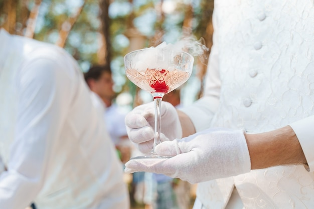 Waiter in white gloves holds wine glass with sparkling wine, red cherry, and white smoke of dry ice and gives to customer