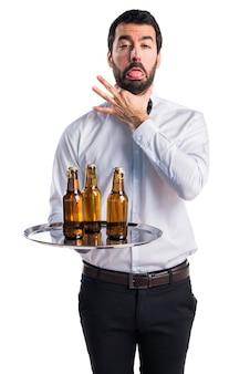 自分自身を溺れさせているトレイにビール瓶を入れたウェイター