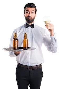 砂時計を保持しているトレイにビール瓶を入れたウェイター