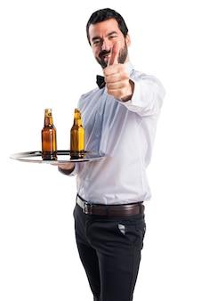 Официант с пивными бутылками на подносе с пальцем вверх