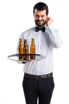 Waiter with beer bottles on the tray covering his ears