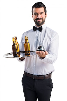 Waiter with beer bottles on the tray holding a bell