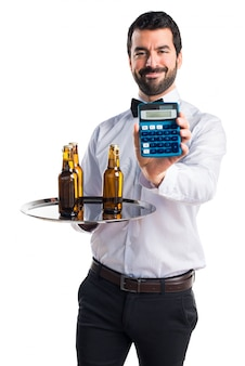 Waiter with beer bottles on the tray holding a calculator