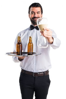 Waiter with beer bottles on the tray holding sand clock