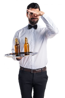 Waiter with beer bottles on the tray making smelling bad gesture