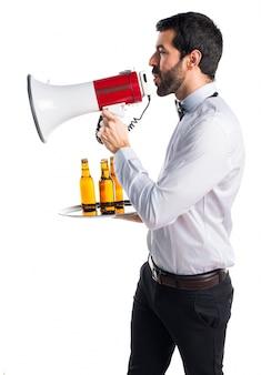 Cameriere con bottiglie di birra sul vassoio gridando dal megafono