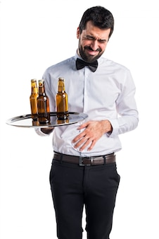Waiter with beer bottles on the tray with stomachache