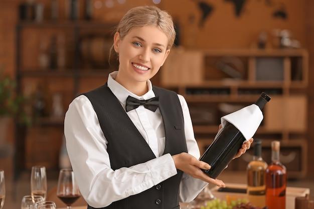 Официант с бутылкой вина в ресторане
