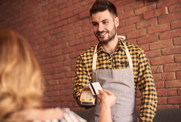 Официант с устройством для чтения кредитных карт в ожидании оплаты