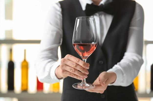 Официант с бокалом вина в баре