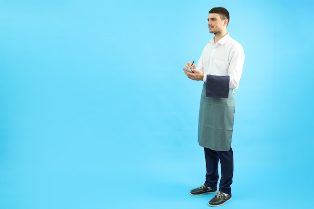 Waiter with notebook on blue background, space for text.