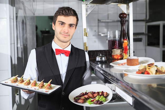 Waiter with a ready prepared dishes in the restaurant kitchen