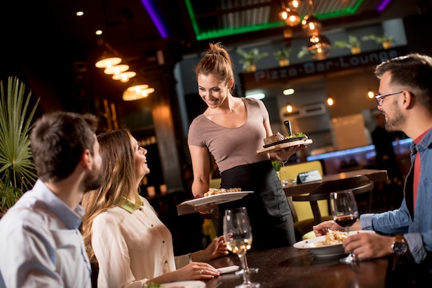 Женщина официанта, обслуживающая группу друзей с едой в ресторане